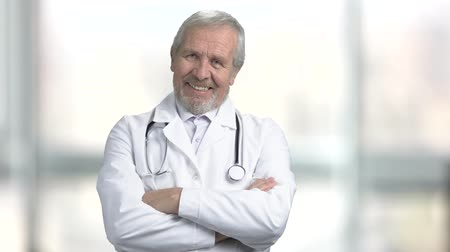hanedan arması : Senior doctor smiling on blurred background. Happy elderly doctor with arms crossed. People, medicine, emotion.