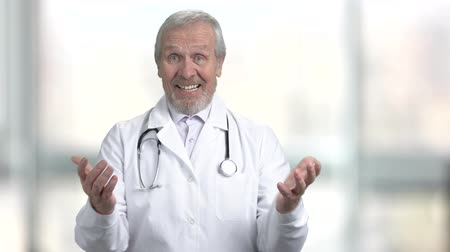 メディケア : Happy surprised senior doctor, portrait. Joyful medical worker clapping hands on blurred background. Human gestures and emotions.