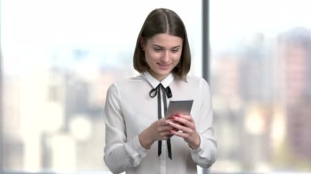 blúz : Young smiling woman using smartphone. Happy cherful female corporate typing a massage using touch screen phone, blurred background. People, business, technology.