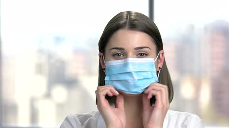 cirurgião : Young cheerful doctor puts on a mask. Happy smiling professional doctor putting on protective mask on blurred background. People, medicine, healthcare.