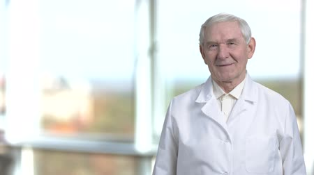 медик : Smiling portrait of senior science specialist in white coat. Cheerful oldman staying at the right in blurred window background.