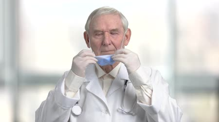 zmarszczki : Put on surgical mask using both hands. Portrait of old grayhaired doctor putting on medical mask in bright blurred room background.