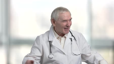 splatnost : Kind old doctor cheering you up. Speech of old cheerful pediatrician, bright blurred windows in hospital background. Dostupné videozáznamy