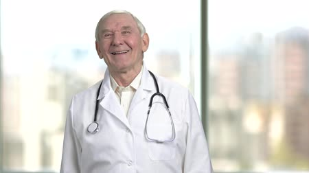 страхование здоровья по старости : Front view cheerful senior doctor laughing hard. Portrait of a jovial old male doctor in lab coat and stethoscope. Bright abstracrt blurred windows background with view on city.