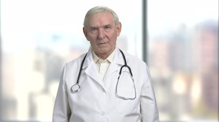 carrancudo : Bad news from the doctor. Portrait of an old serious nervous stressed doctor getting ready to tell bad news to a patient. Bright abstract blurred windows background with view on city. Stock Footage