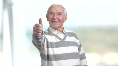 happiness symbol : Senior man showing thumb up. Happy grandfather giving thumb up, blurred background. Human emotions and gestures. Stock Footage