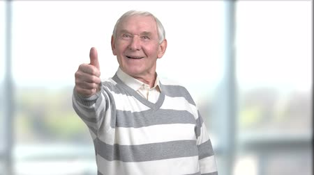 vrásčitý : Cheerful senior man giving thumb up. Happy retired man showing thumb up on blurred background.