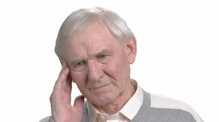 cheerless : Aged man suffering from migraine. Grey haired man having pain in his temple, isolated on white background. Migraine and headache concept.