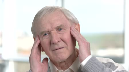 cheerless : Cheerless old man having strong headache. Sad aged man massaging his temples as suffering from headache. Stock Footage