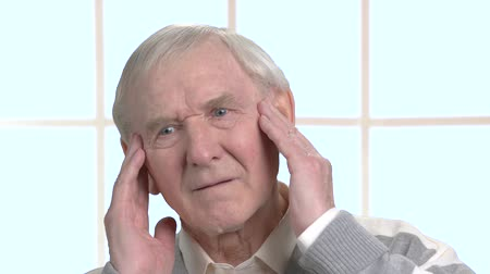 cheerless : Worried old man massaging his temples. Sad elderly man having strong headache, window background. Human health problems and facial expressions. Stock Footage