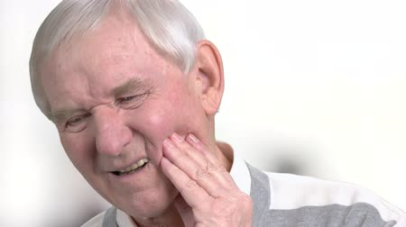 зубная боль : Elderly man suffering from strong tooth pain. Close up senior person suffering from painful teeth. Dental care and health, medical concept.