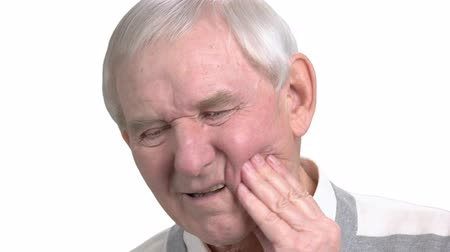 зубная боль : Close up man suffering from toothache. Old man with toothache, white background. How to stop toothache. Remedy for tooth ache. Стоковые видеозаписи