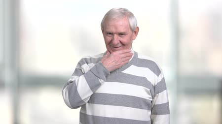 contemplative : Old smiling man touching his chin. Elderly thoughtful man having a plan, blurred background. Strategy thinking of senior man. Stock Footage