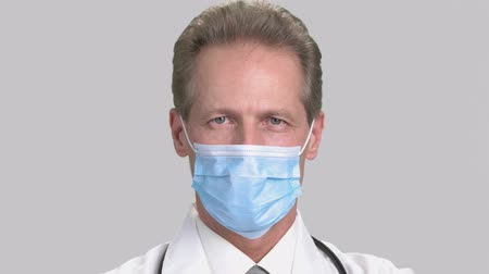 protective suit : Close-up portrait of serious man doctor in white surgical mask. Mature friendly caucasian smiling physician, grey isolated background. Stock Footage