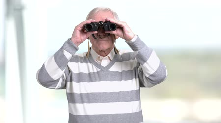 binocular : Senior man looking through a pair of binoculars. Grandfather looking into binoculars and looking for something, blurred background.