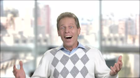 vay : Happy shocked man on blurred background. Joyful mature man with funny face looking surprised in full disbelief hands, window city background. Facial expresssions and body language. Stok Video