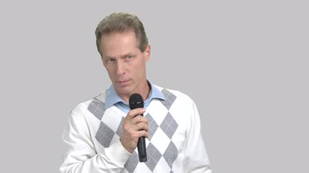 press conference : Mature caucasian man with microphone. Middle-aged european man talking with microphone on grey background. Business seminar or presentation concept.