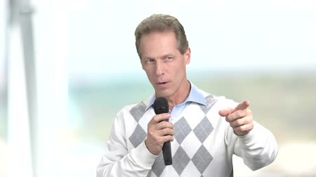 interativo : Man with microphone pointing with finger. Man with a microphone chooses the participants of the training, blurred background. Interactive communication concept.