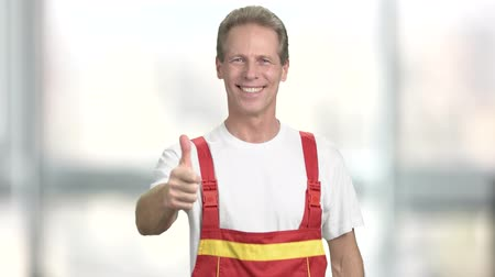 taça : Happy engineer gesturing thumb up. Smiling manual worker showing thumb up on blurred background. Sign of success. Stock Footage