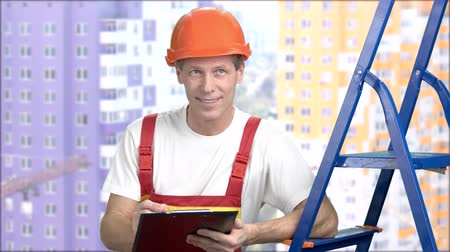 supervisora : Cheeful foreman on buildings background. Smiling mature construction engineer sketching on clipboard. People, repair, engineering.