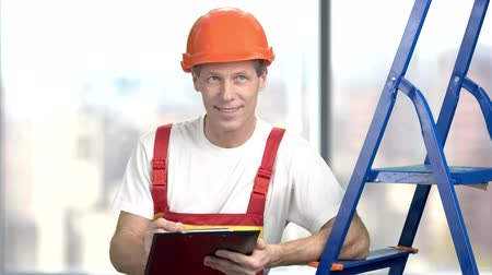 supervisora : Smiling builder writing on clipboard. Handsome foreman in uniform leaning at ladder and making a note on clipboard, blurred background. Archivo de Video