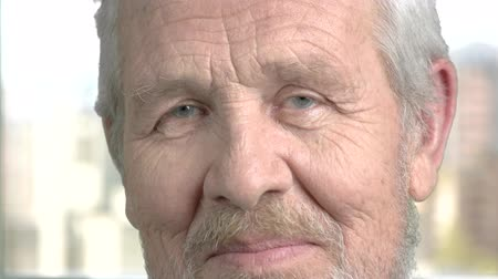 expectancy : Elderly man looking cautious close up. Close up face of aged man looking suspicious, blurred background.