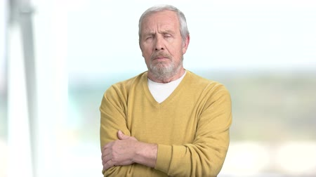 gripe : Elderly man with crossed arms. Senior man in casual sweater having sudden headache, blurred background.