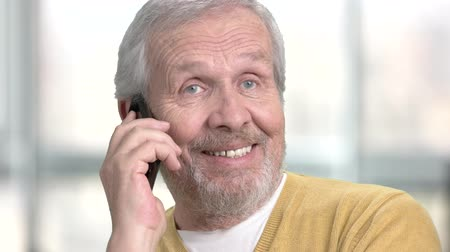 представитель старшего поколения : Friendly caucasian pensioner talking on phone. Close up senior european man with mobile phone on blurred background.