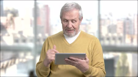 引退する : Happy aged man using pc tablet. Cheerful elderly man talking via internet using digital tablet, blurred background.