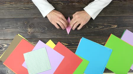 dobrável : Hands making pink orizuru figurine. Man forming traditional paper crane, top view. Origami tutoring lessons.