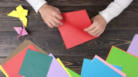 talent : Male hands folding red paper sheet. Origami folding background. Japanese art concept. Stock Footage