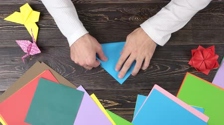 dobrável : Male hands folding blue paper. Man making origami crane, top view. How to make origami crane.