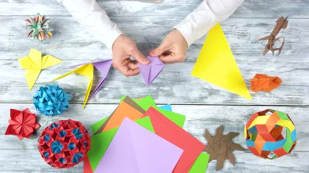 motyl : Hands doing origami swallows. Person making plane from colorful paper. How to fold a super easy and quick origami birds.