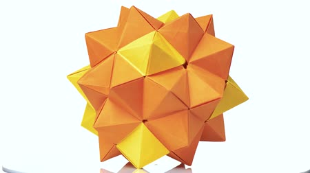 сложить : Modular origami figure on white background. Yellow origami ball. Paper folding and geometry. Стоковые видеозаписи