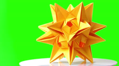 折り紙 : Spiky origami model on green screen. Origami star figurine on board. Modern kusudama art.