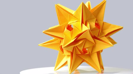 spiky : Yellow origami star on gray background. Beautiful result of art school. Modular technique of kusudama art. Stock Footage