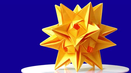 spiky : Origami cosmic body on blue background. Spiked origami figure of yellow color. Complex paper work. Stock Footage