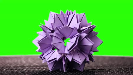 spiky : Violet origami flower on green screen. Spiky origami model on chroma key background. Trendy kusudama art.