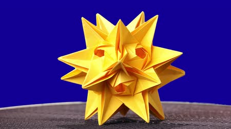 spiky : Beautifully folded kusudama figure. Yellow origami star on blue background. Creativity of kusudama craft. Stock Footage