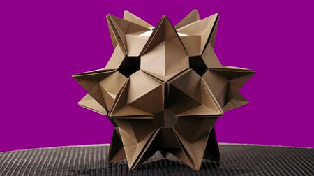 spiky : Spiky origami figure on colorful background. Celestial body made from cardboard on pink background.