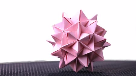 spiky : Stellated origami ball on white background. Spiky origami decoration isolated on white background. Modular cardboard product. Stock Footage