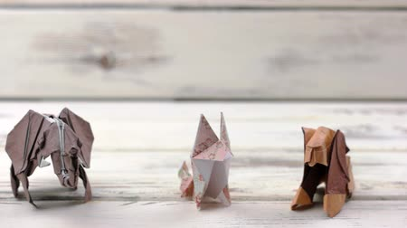 heykelcik : Set of origami animals on wooden background. Collection of paper animal models on white wooden table. Exhibition of japanese paper art.