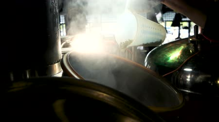 literário : Grain sprinkle into steaming brewery kettle. Sprinkle the entire content of Measuring cup. Stock Footage