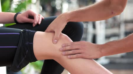 kotník : Girl injured her leg during gym training. Male hands doing a massage to female knee at gym close up. Training accident concept.