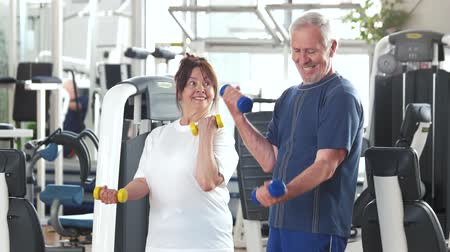 strong granny : Couple of seniors training with dumbbells. Elderly couple working out together at gym. Sport as kind of leisure. Stock Footage