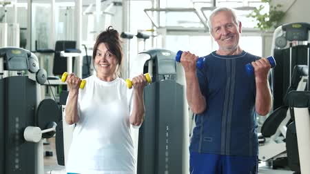 strong granny : Couple of seniors training at gym. Smiling older people exercising with dumbbells at fitness club. Elderly people and sport.