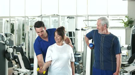 strong granny : Personal trainer helping lift dumbbells to seniors. Happy senior couple lifting dumbbells while male instructor guiding them. Easy strength training workouts.