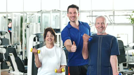 strong granny : Couple of seniors lifting dumbbells at gym. Friendly personal trainer at a fitness center helping to seniors. Fitness trainer showing thumb up. Benefits of strength training exercises for seniors.