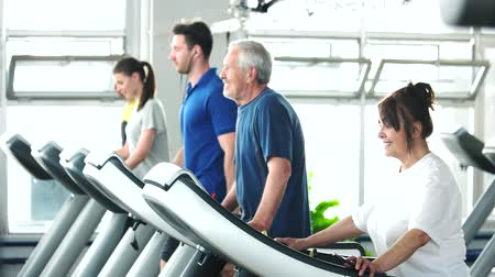 strong granny : Senior woman running on treadmill at gym. Elderly woman runs on treadmill and looking at her smartphone. People, sport and technology. Stock Footage