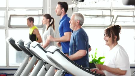 strong granny : Energetic senior woman exercising on treadmill. Group of people of differrent ages training at gym. Always be in fit.